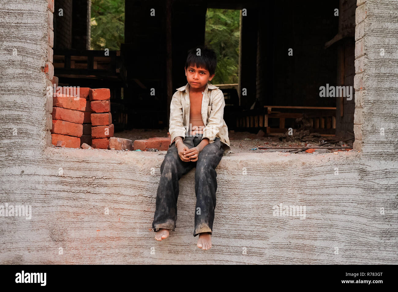 New delhi, India - 20 october 2017: portrait of young indian boy working as bricklayer in construction with dirty clothes and sad face with resignatio - Stock Image