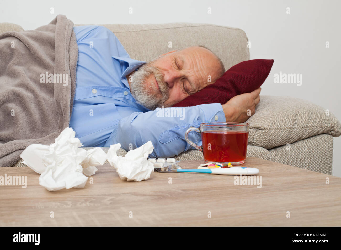 Sick senior male patient lying on the couch at home - Stock Image