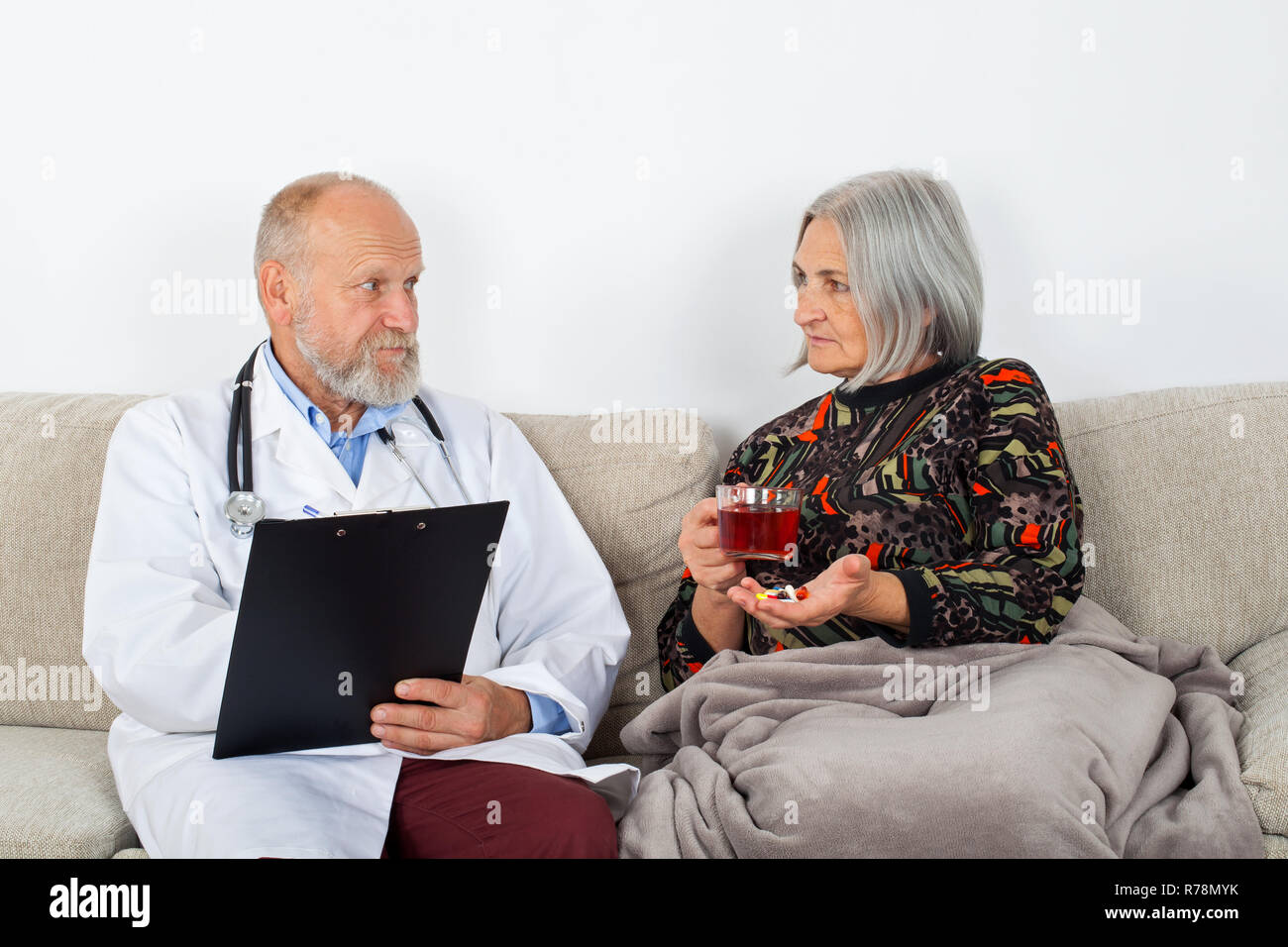 Doctor with clipboard diagnosing an elderly patients at home - Stock Image