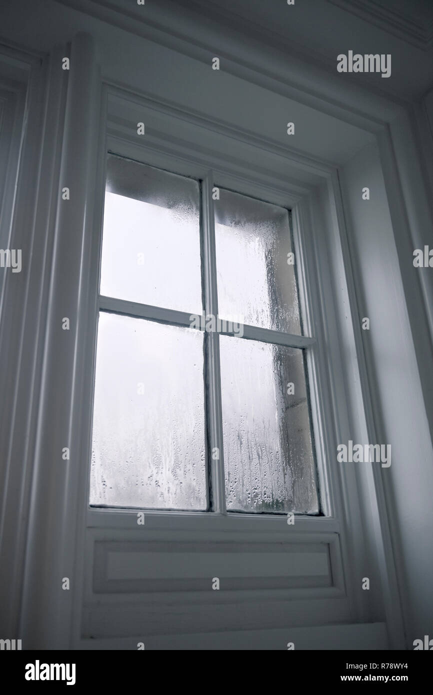 Looking out through an old white painted wood framed sash window, with condensation on the glass panes. - Stock Image