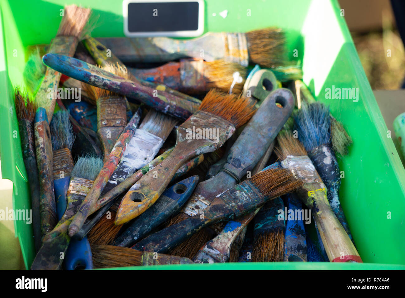 ARTIST's POUCH OF PAINT BRUSHES. Rustic painter s brushes of various shapes and sizes in an old leather pouch attached to one side of a table - Stock Image