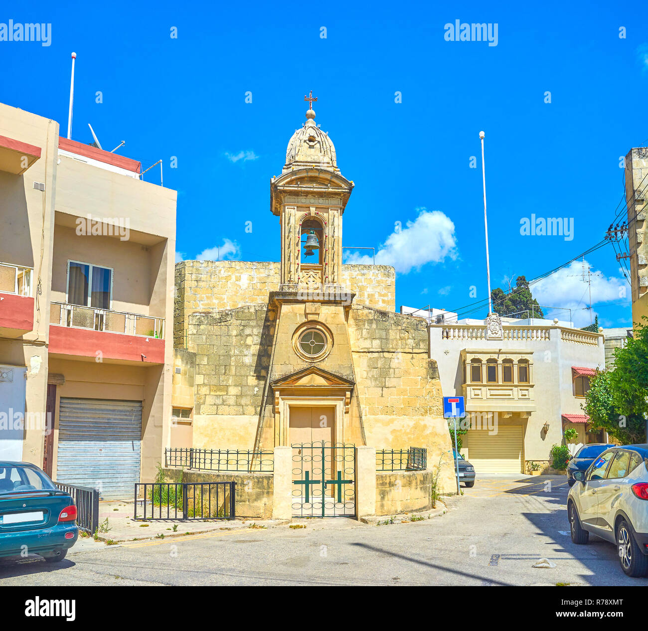 The old small church with bell tower located in residential neighborhood of Mosta town, Malta - Stock Image