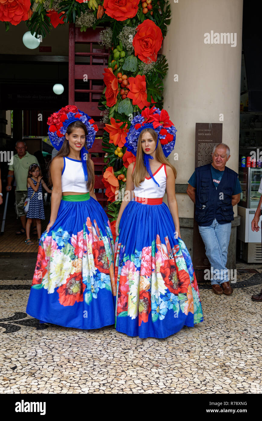 Two young women in colourful versions of Tradional Costume with large pleated skirts and flowery headpieces in the city of Funchal on Madeira - Stock Image