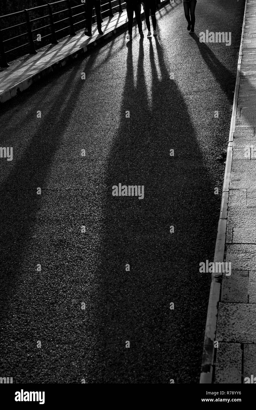 Long evening shadows of four young persons, friends, walking towards the camera, black and white image, partial legs, feet, Sun light reflection - Stock Image