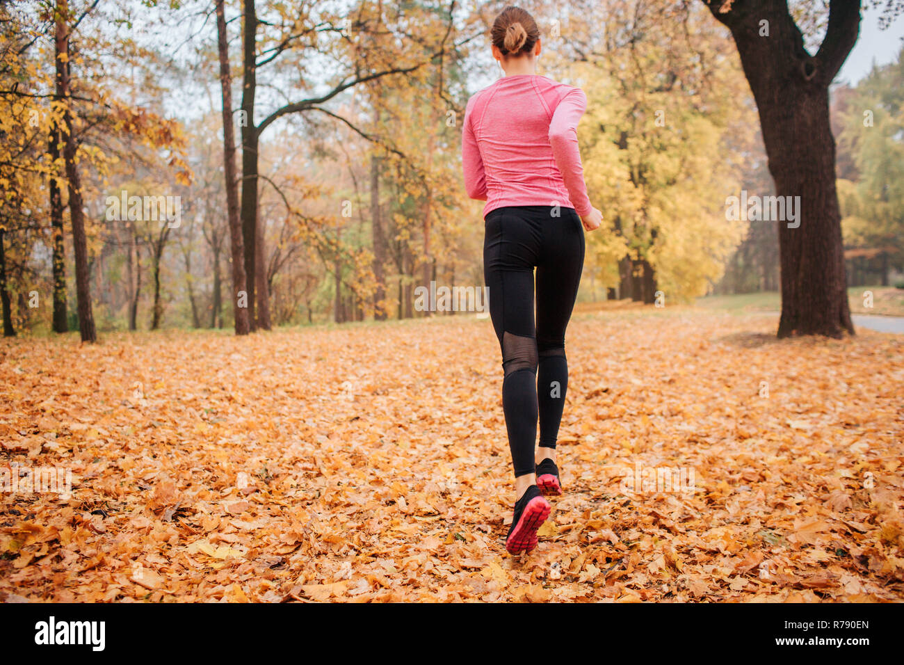 Picture of young woman running in park. It is chilly weather outside. Orange leaves lying on ground. Young woman jogging. She run alone. - Stock Image