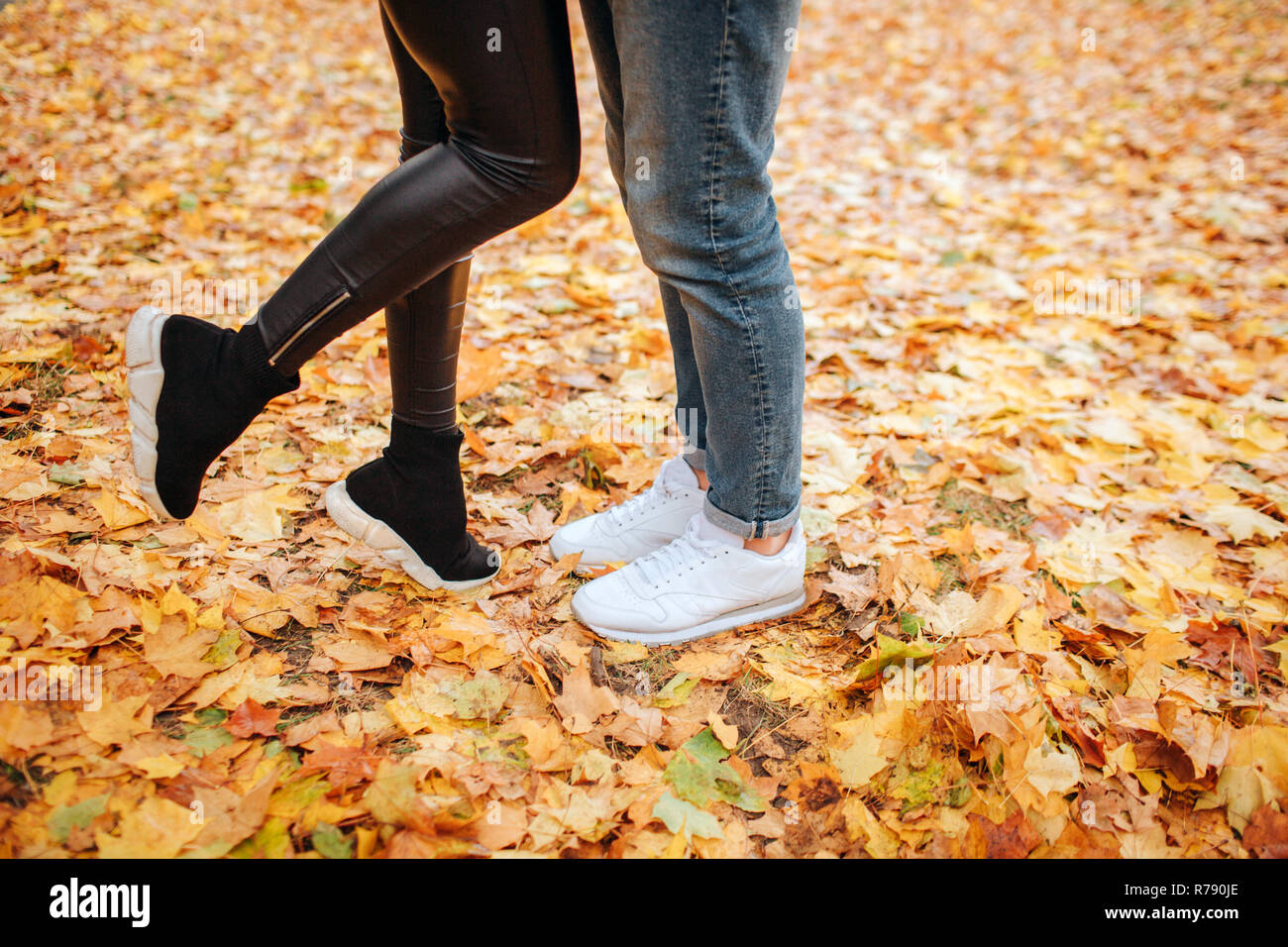 Cut vuew of young man and woman legs. He stands on two. She holds one feet up. They stand on yellow leaves. - Stock Image
