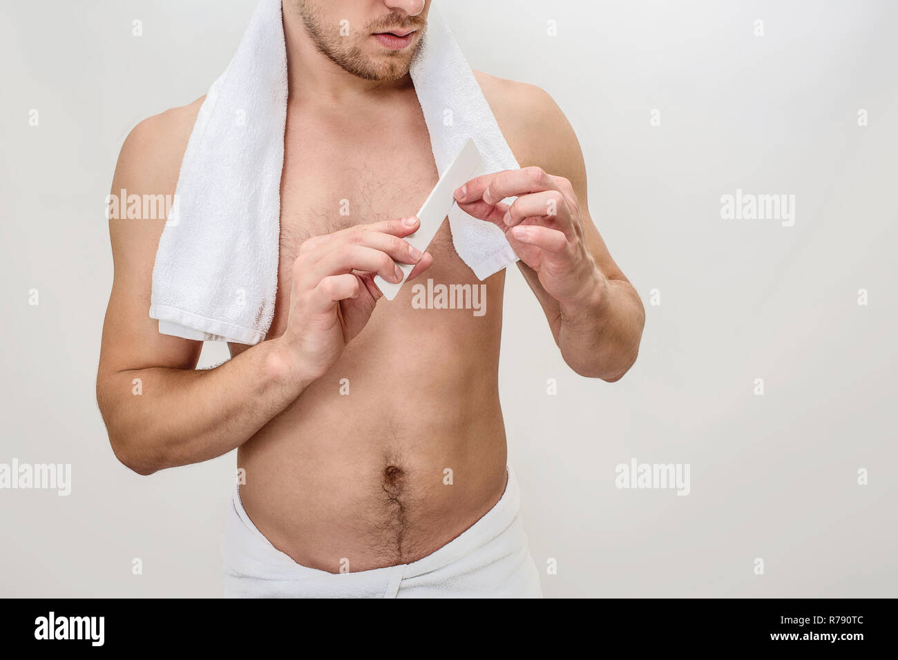 Cut view of well-built young man does nail up correction. He has towel around neck. Guy is shirtless. Isolated on white background. - Stock Image