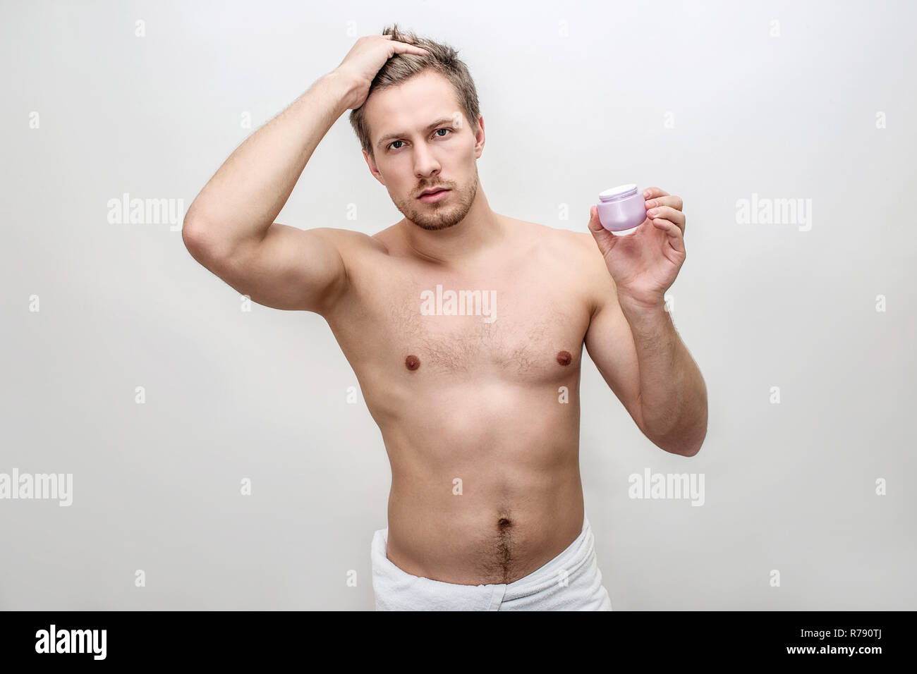 Young male model hold one hand on hair. He poses on camera. Face cream is in another hand. Isolated on white background. - Stock Image