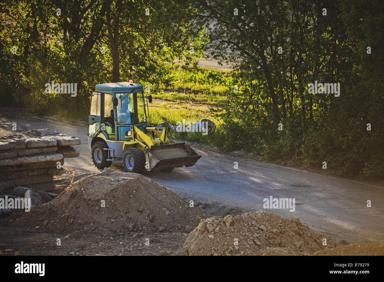 Small excavator car moving on a dusty road through construction place in sunset light - Stock Image