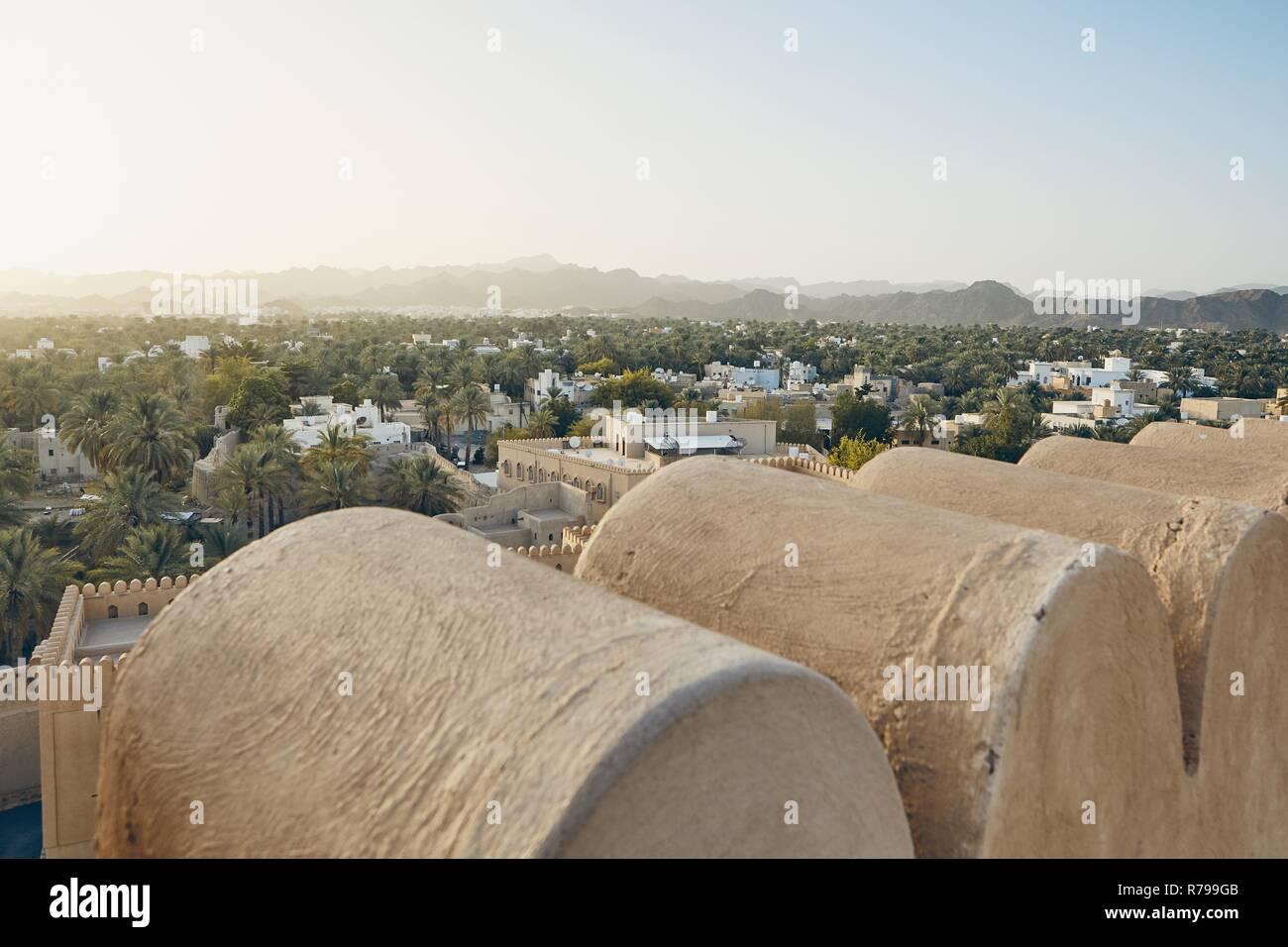 City against mountain range at idyllic sunset. Nizwa in Sultanate of Oman. Stock Photo