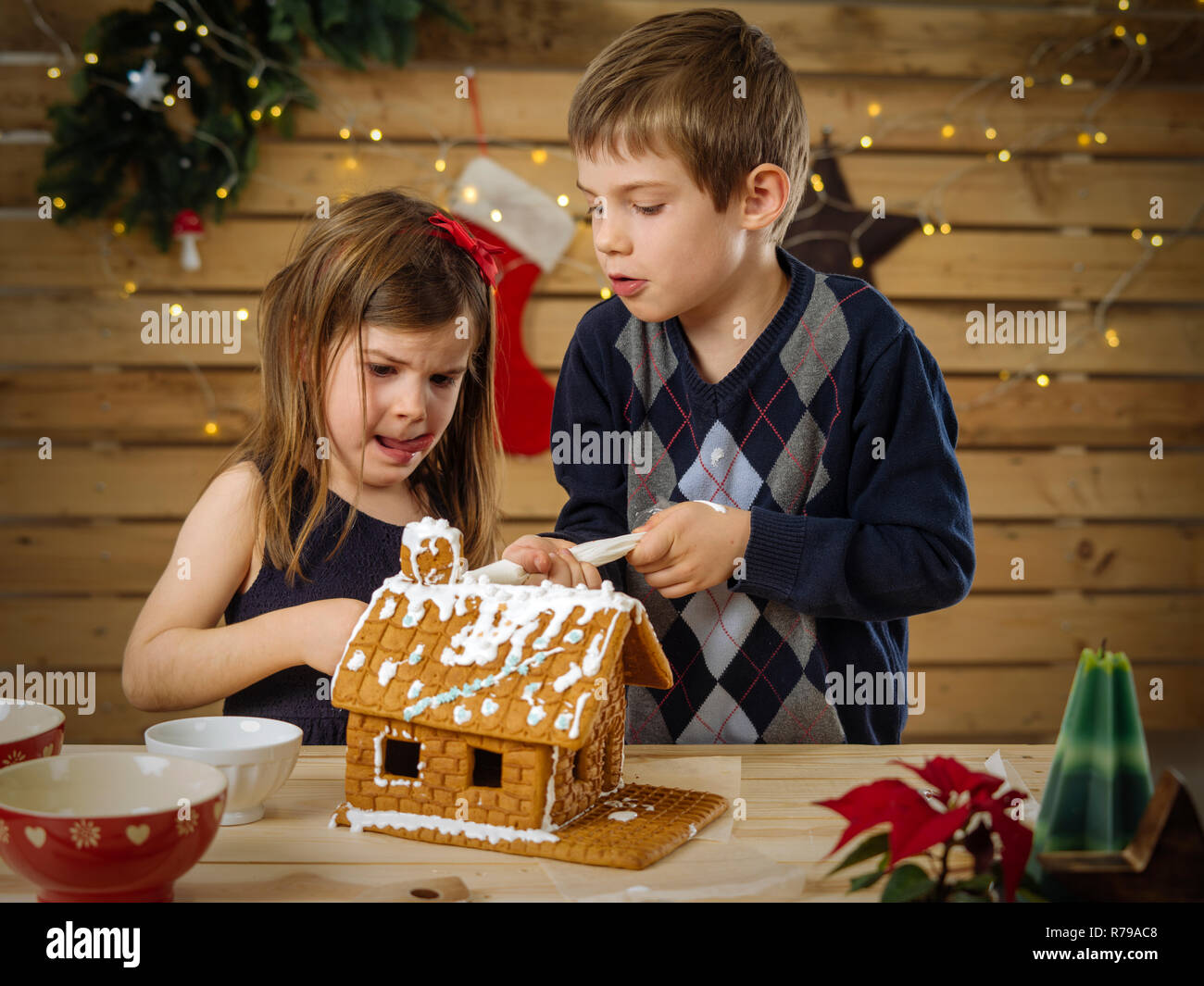 Photo of a young brother and sister decorating a gingerbread house at home just before Christmas. - Stock Image