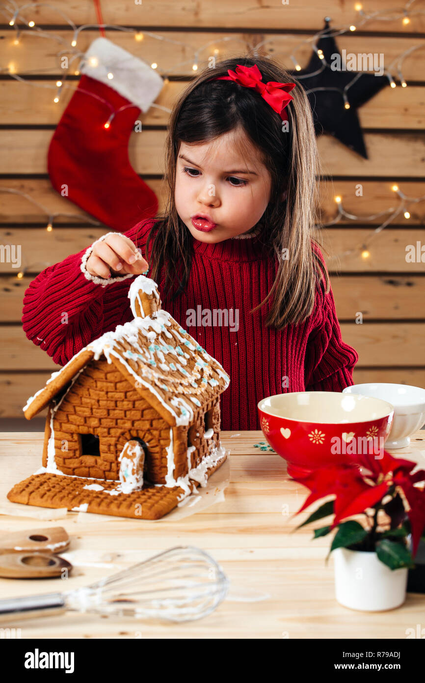 Photo of a young girl decorating a gingerbread house at home just before Christmas. - Stock Image