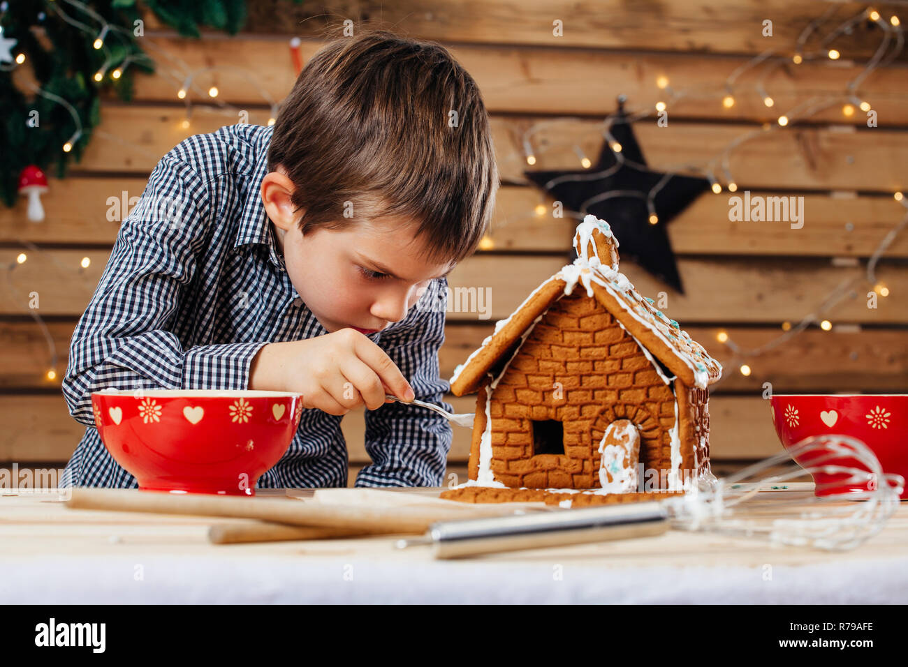 Photo of a young boy decorating a gingerbread house at home just before Christmas. - Stock Image