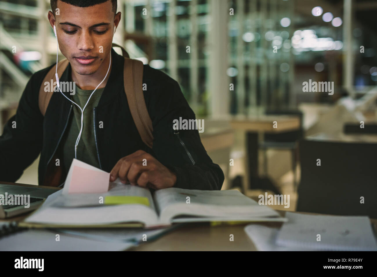 Male student sitting at table reading books and preparing for exams. Young man reading book at university library. - Stock Image