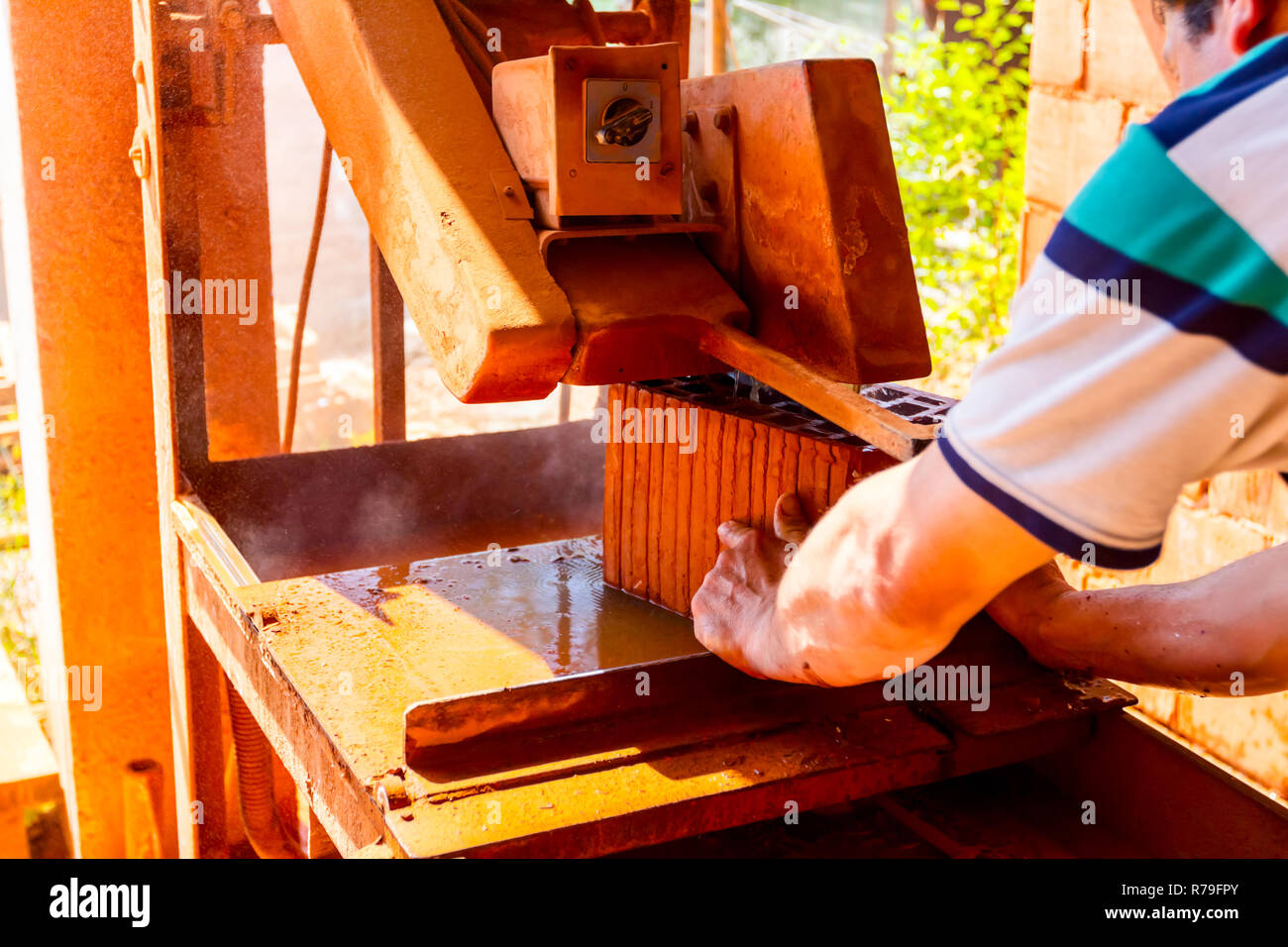 Worker is using power tool to makes clean precise cut in red brick, block. It uses abrasive action to slice through material as the saw rotates at hig - Stock Image