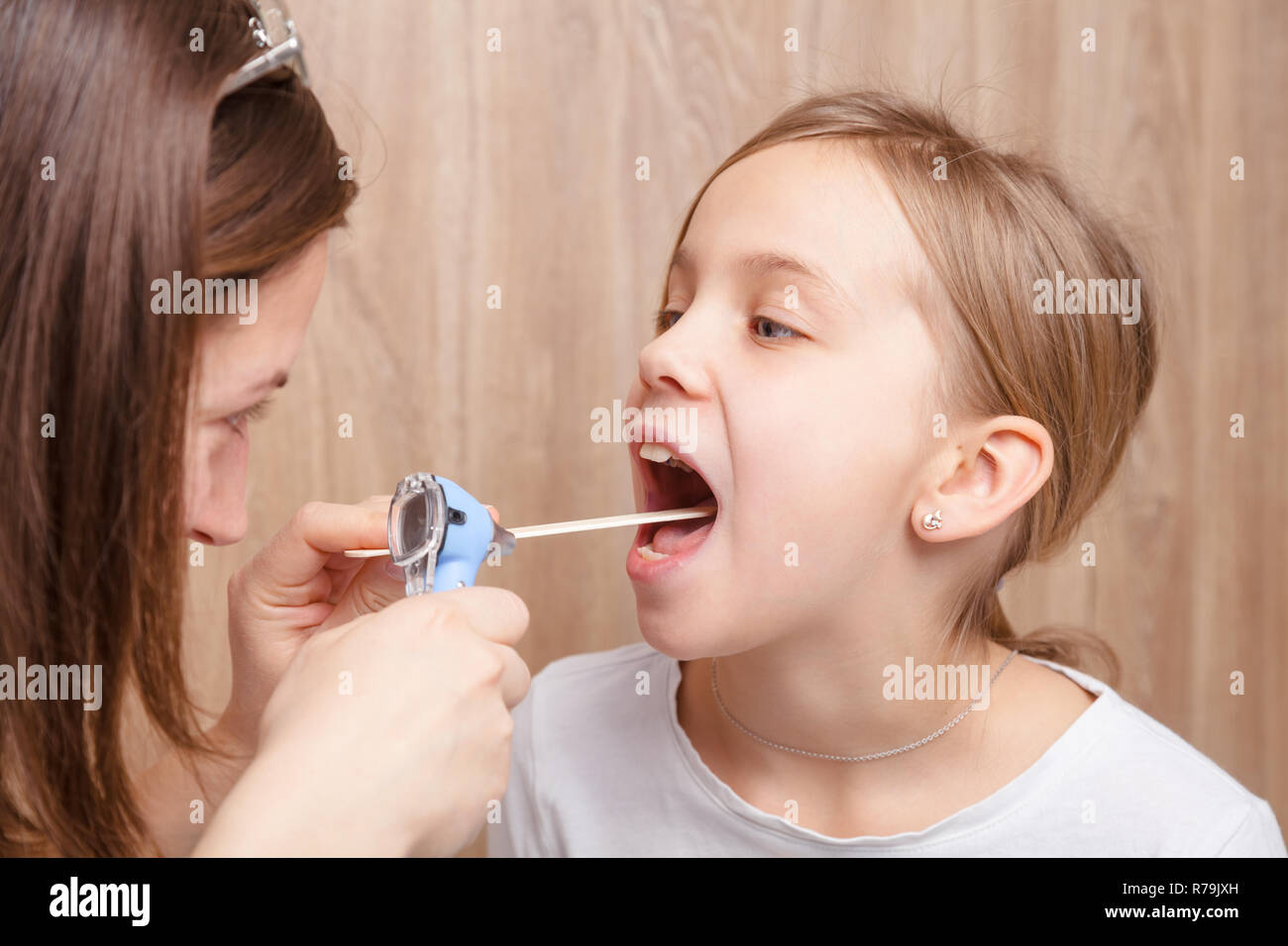 Female pediatrician or health care practitioner examines elementary age girl's throat using wooden tongue depressor and torch. Child physical examinat - Stock Image