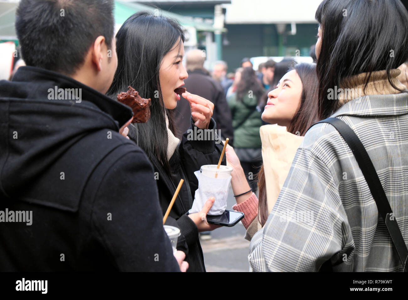 Young Chinese people tourists eating snack food, brownies at outdoor street food Borough Market in Southwark South London UK   KATHY DEWITT Stock Photo