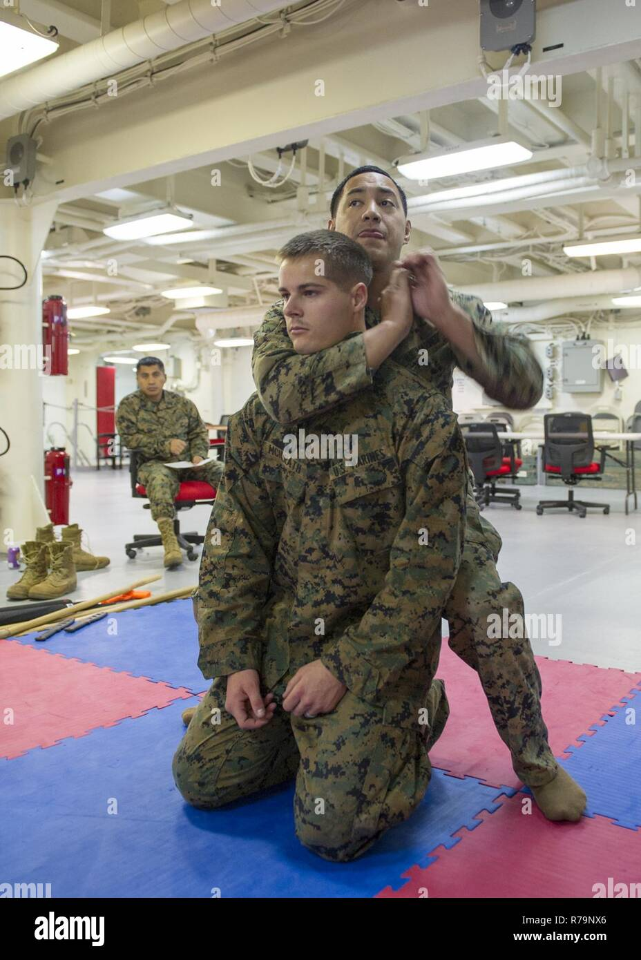 PACIFIC OCEAN (April 10, 2017) Marine Lance Cpl. Stefan Mcilrath (front) and Staff Sgt. Kaluaokal Kaiahua (back), both assigned to Marine Expeditionary Unit (MEU) 15, practice mixed martial arts during a Marine Corps Martial Arts Program (MCMAP) training exercise aboard the amphibious assault ship USS America (LHA 6). America is currently underway with more than 1,000 Sailors and 1,600 embarked Marines conducting Amphibious Squadron/Marine Expeditionary Unit Integration operations in preparation for the ship's maiden deployment later this year. - Stock Image