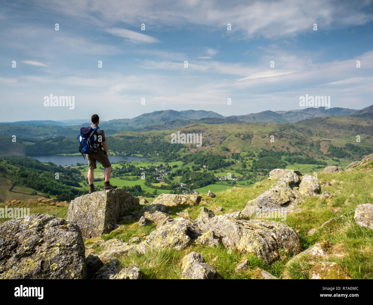 A man enjoys the view towards Grasmere from Stone Arthur, a rock formation in the Lake District, Cumbria, England. Stock Photo