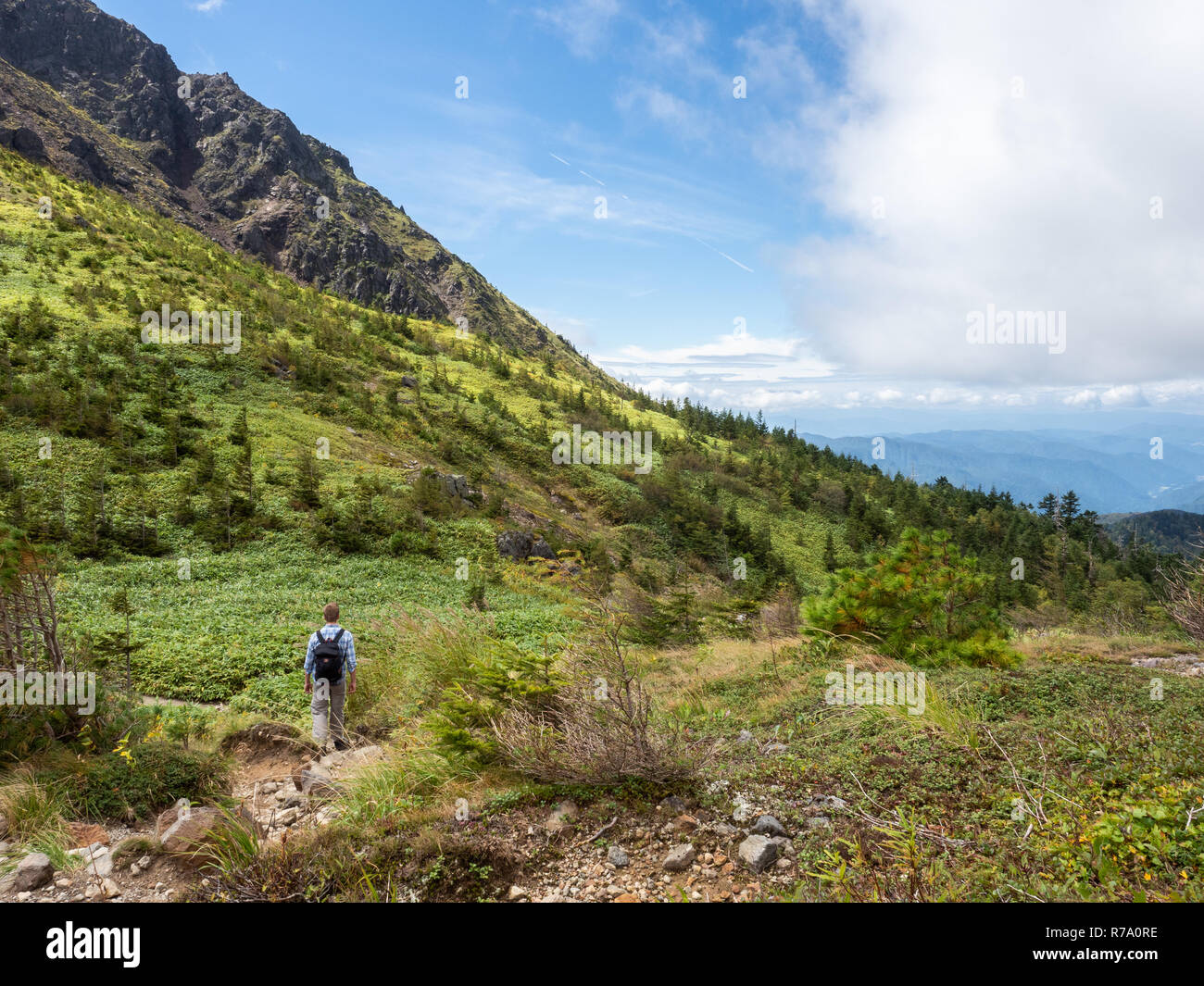 A hiker approaching the summit of Mount Yake, a volcano in Kamikōchi (the Upper Highlands) in the Hida Mountains, Nagano Prefecture, Japan. Stock Photo