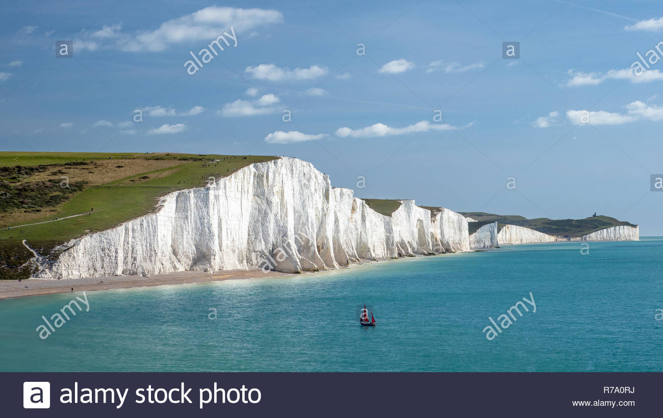 A yacht with red sails seen in the English Channel by the Seven Sisters, chalk cliffs in East Sussex, England. Stock Photo