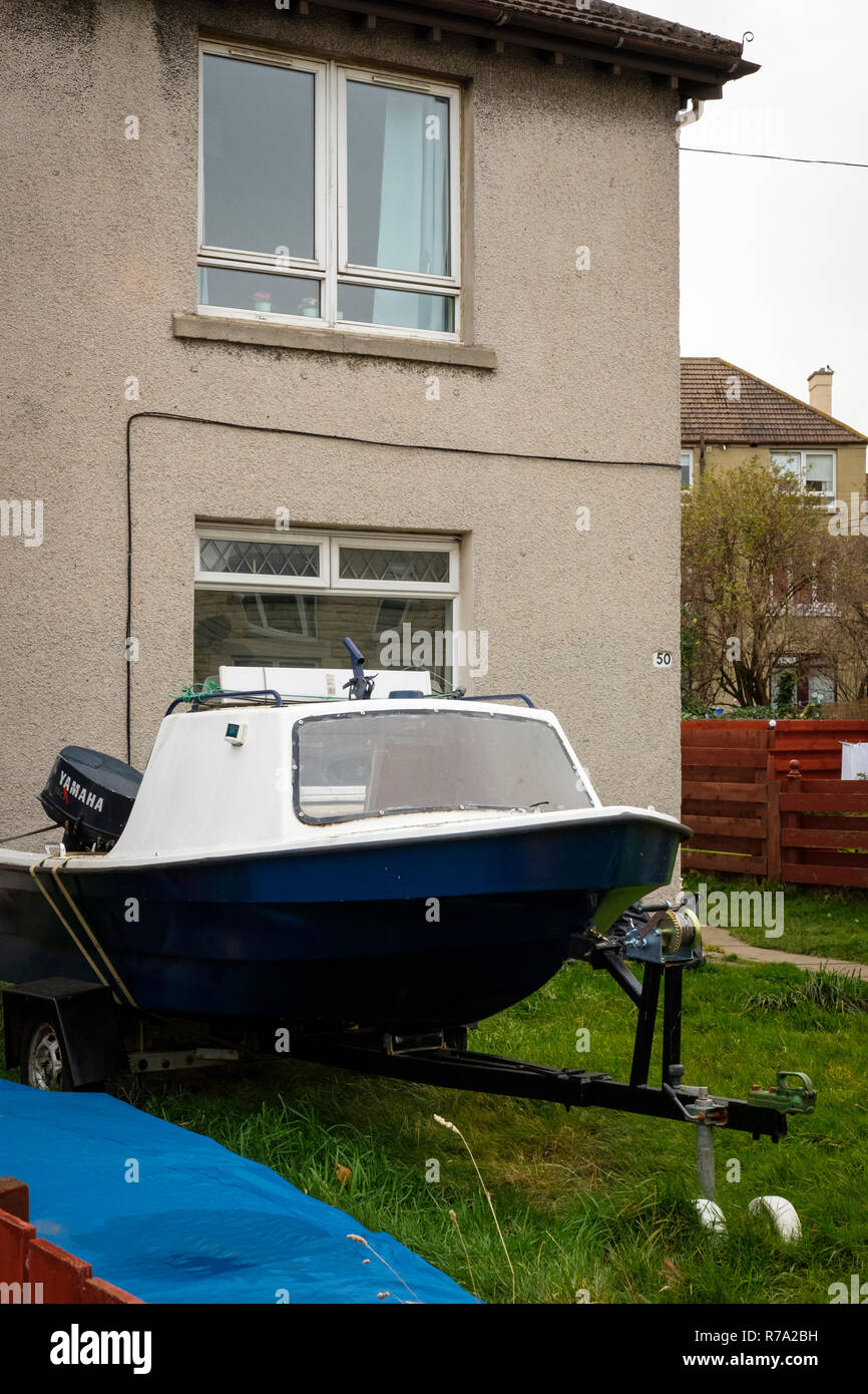 A boat on a trailer, in the front garden of a house in the Restalrig district of Edinburgh, Scotland. - Stock Image