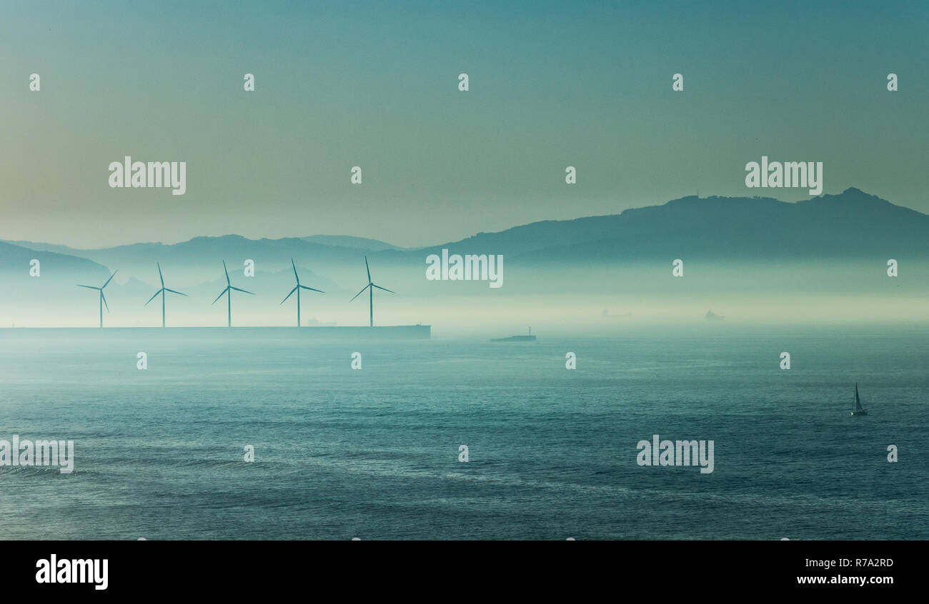 Windmill under the sea mist at dusk, Basque Country - Stock Image