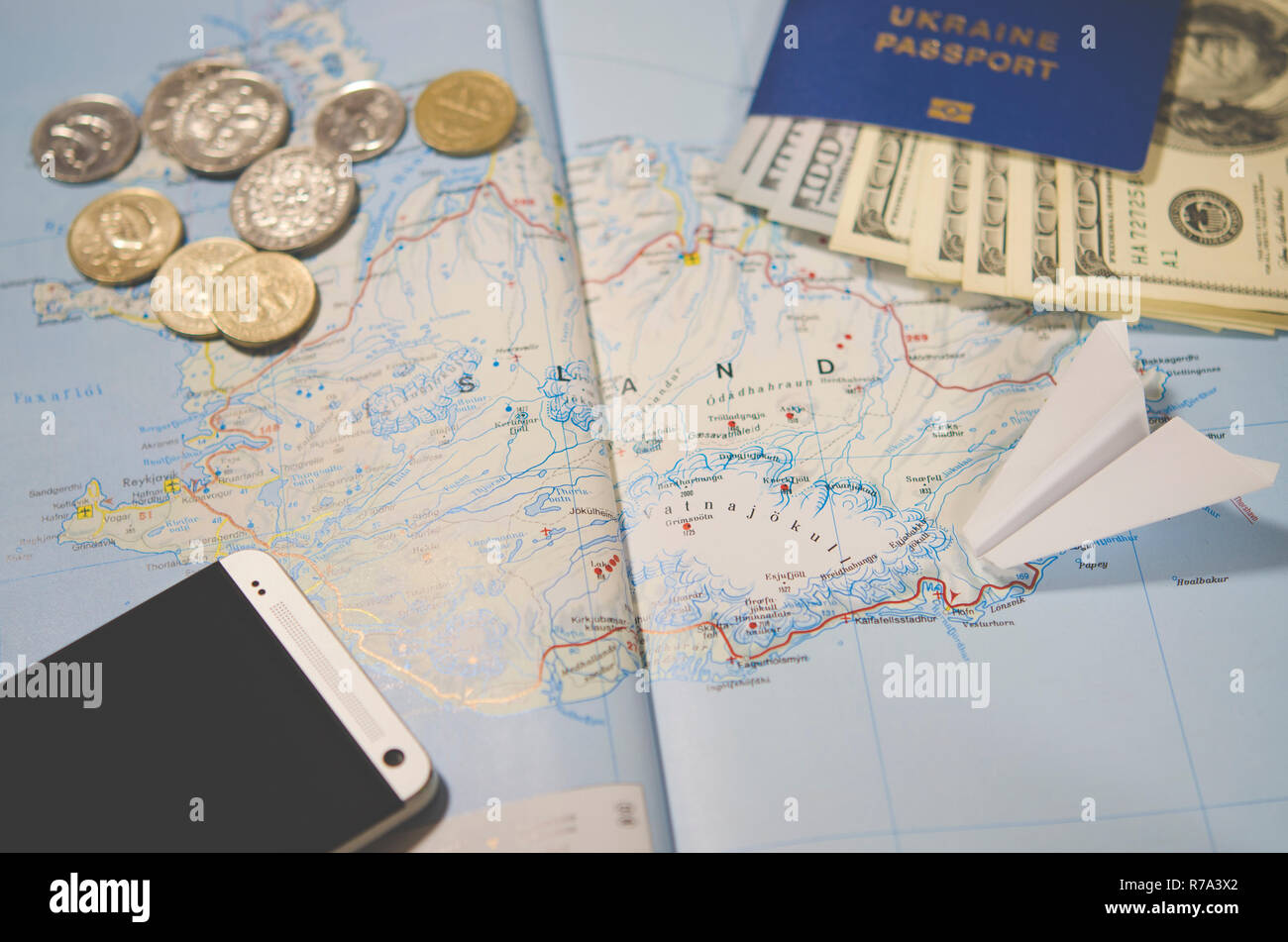 The plane, smartphone, biometric passport, dollars, coins and credit cards lie on a map of Iceland Stock Photo