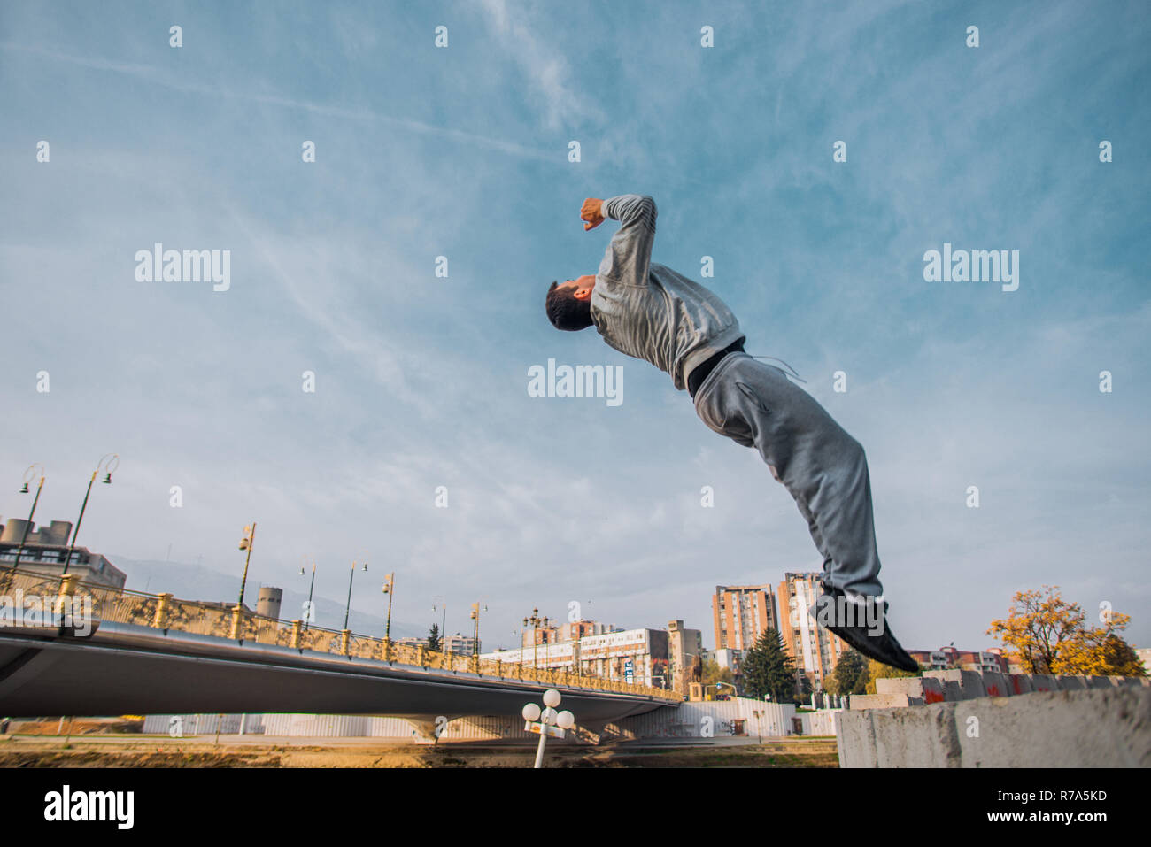 Traceur training parkour jumping at urban place - Stock Image