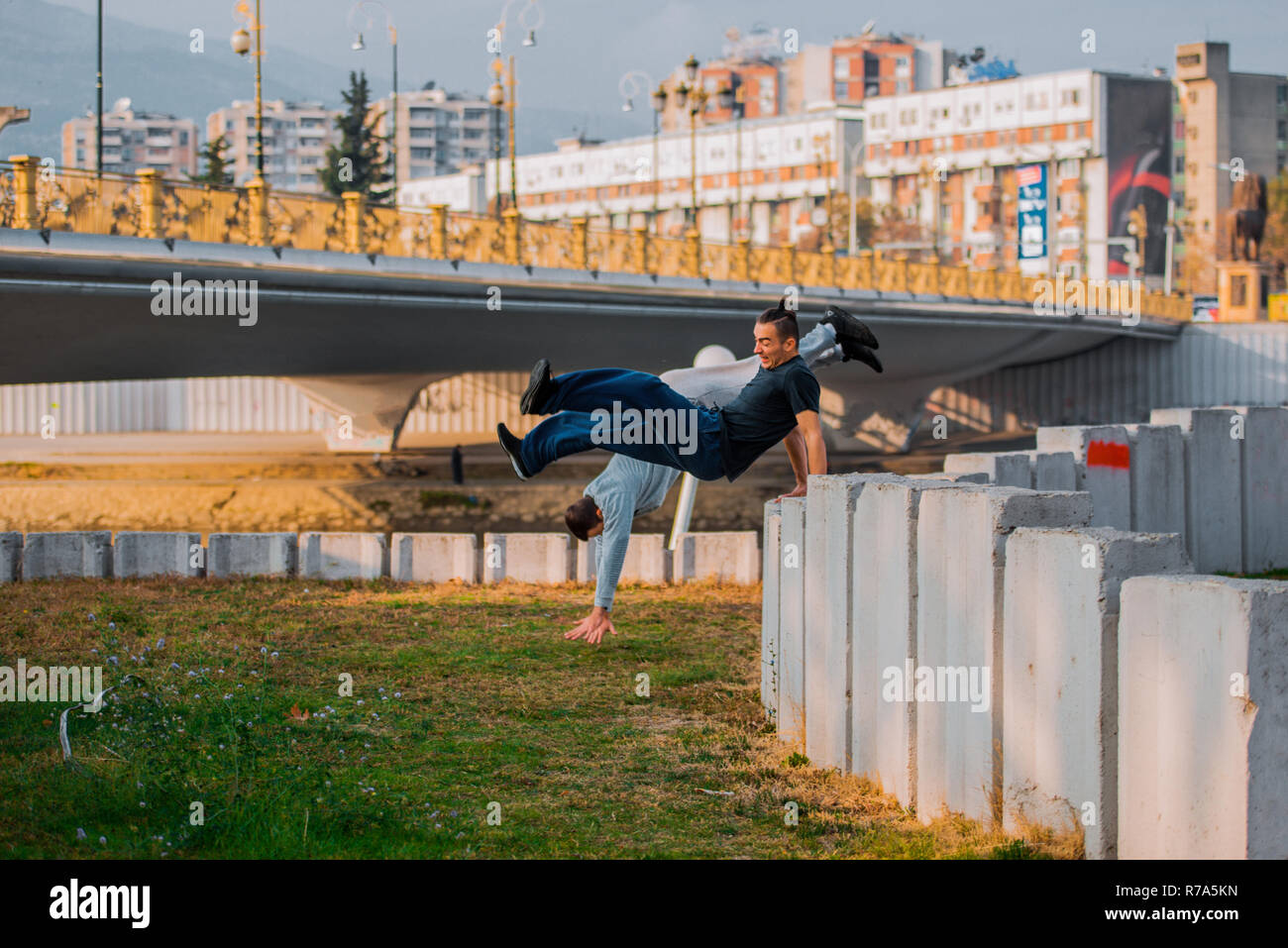 Two stuntman training parkour while jumping over high wall - Stock Image