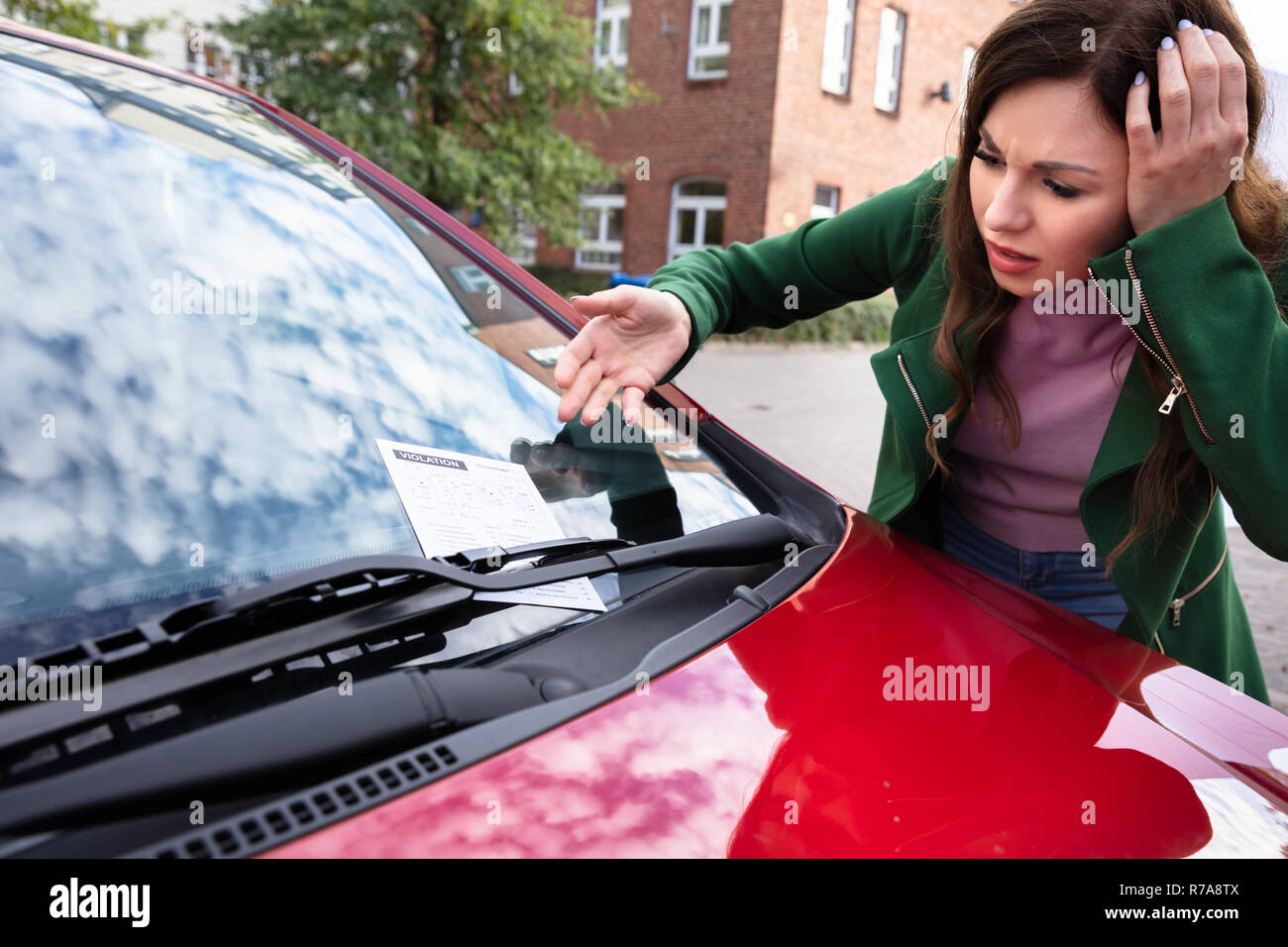 Upset Young Woman Looking At Ticket Fine For Parking Violation On Red Car - Stock Image
