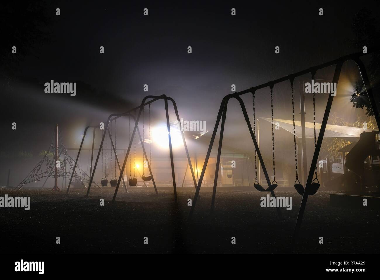 Swing sets backlit by streetlights on a dark foggy morning. Lake Benson Park in Garner North Carolina. Has a haunting or sci-fi feel. - Stock Image