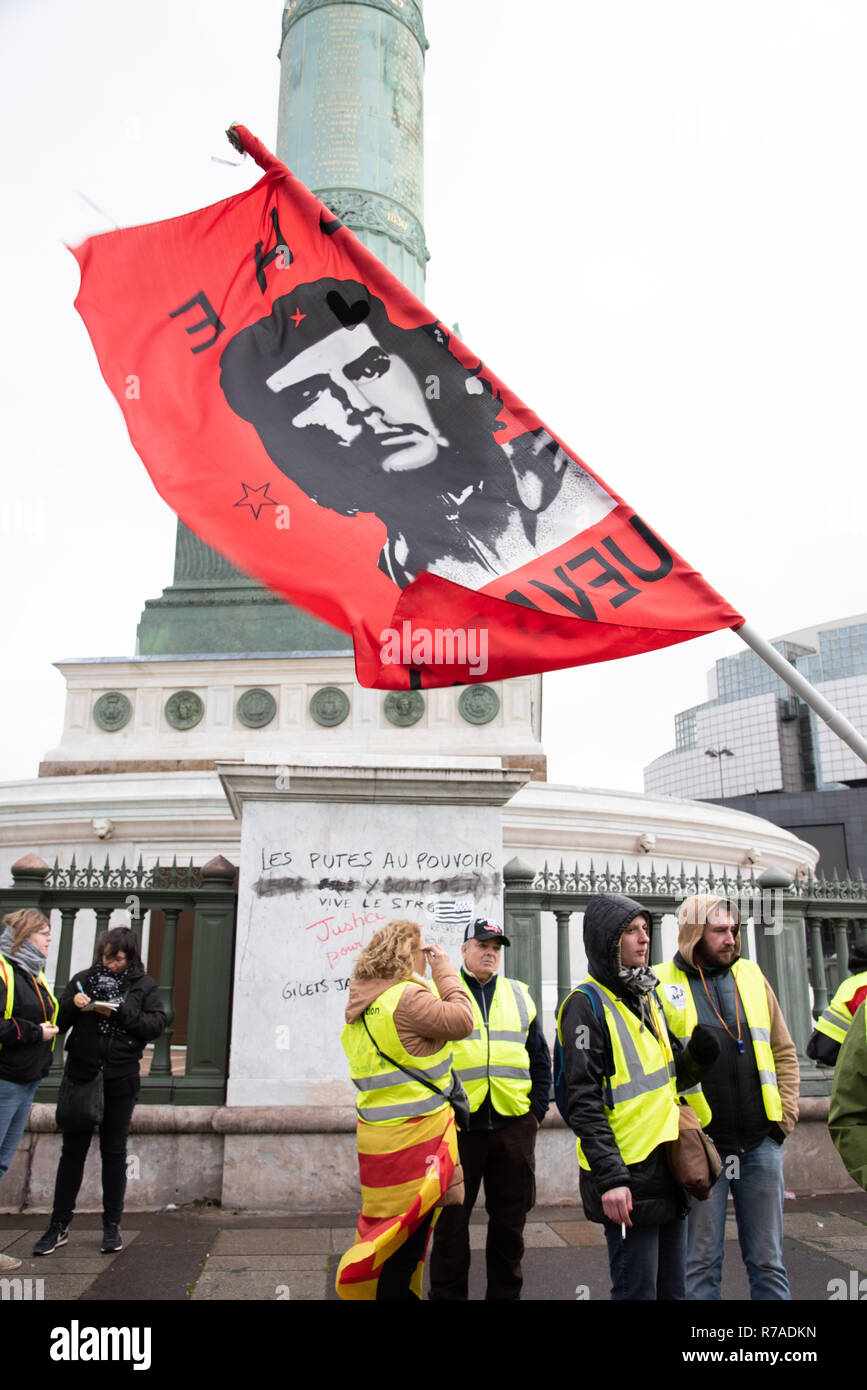 Paris, France, 8th Dec, 2018. Protesters wearing yellow vests holding a flag with the image of Che Guevara in Place de la Bastille, Paris. About 10,000 protesters wearing yellow vests demonstrated in Paris for the fourth weekend in a row to protest against taxes on fuel and decrease in purchasing power, some demanding resignation of French President Emmanuel Macron. Credit: Christelle Chanut/Alamy Live News - Stock Image