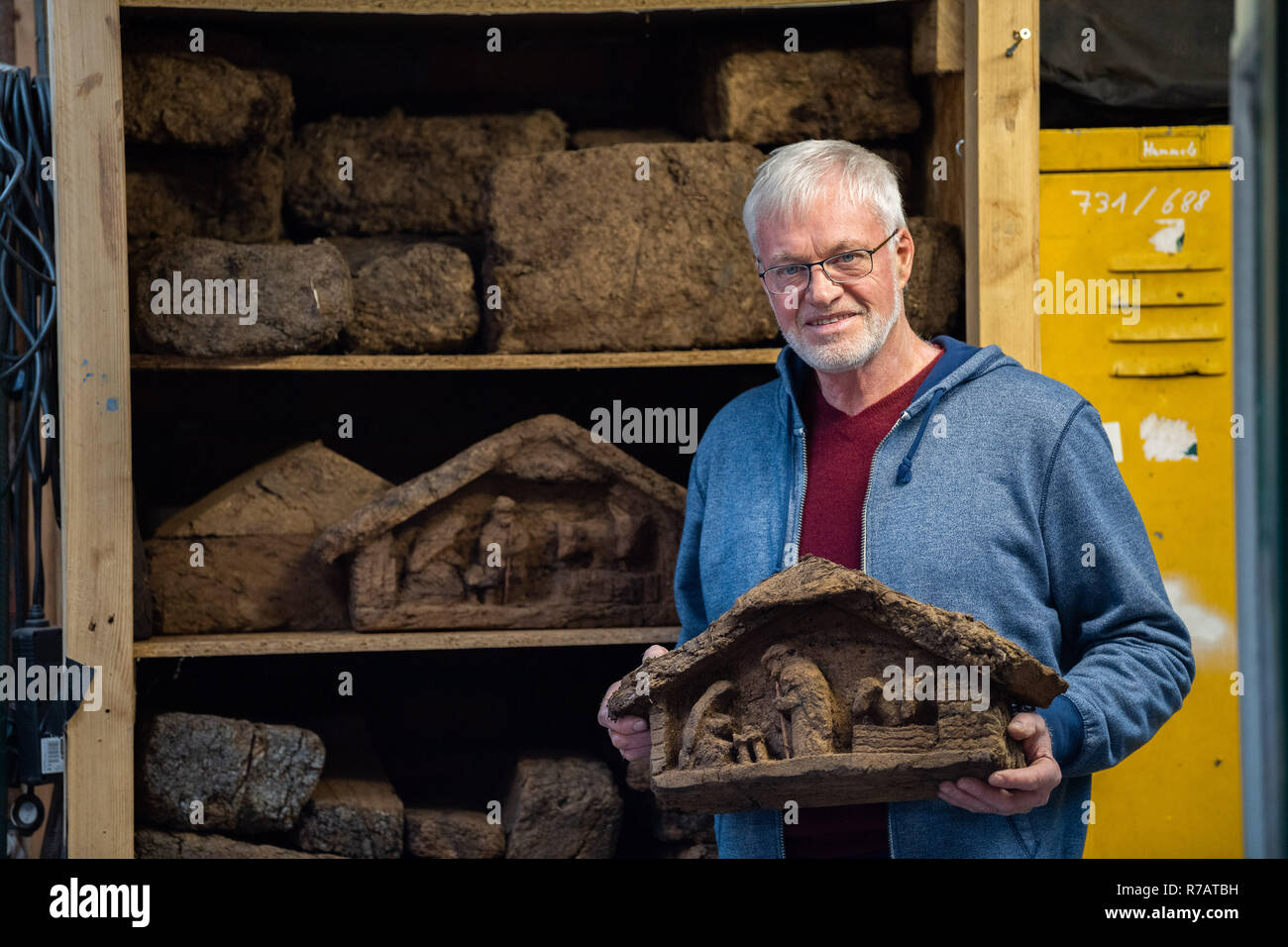 Saterland, Germany. 22nd Nov, 2018. Karl-Heinz Brinkmann holds a Christmas crib carved from peat in front of a shelf with processed and unprocessed peat in his home workshop. The 64 year old Saterland artist works with many materials. But the dried white peat is special: it is 2000 years old. (to dpa '2000 years old: Christmas cribs from peat' from 09.12.2018) Credit: Mohssen Assanimoghaddam/dpa/Alamy Live News - Stock Image