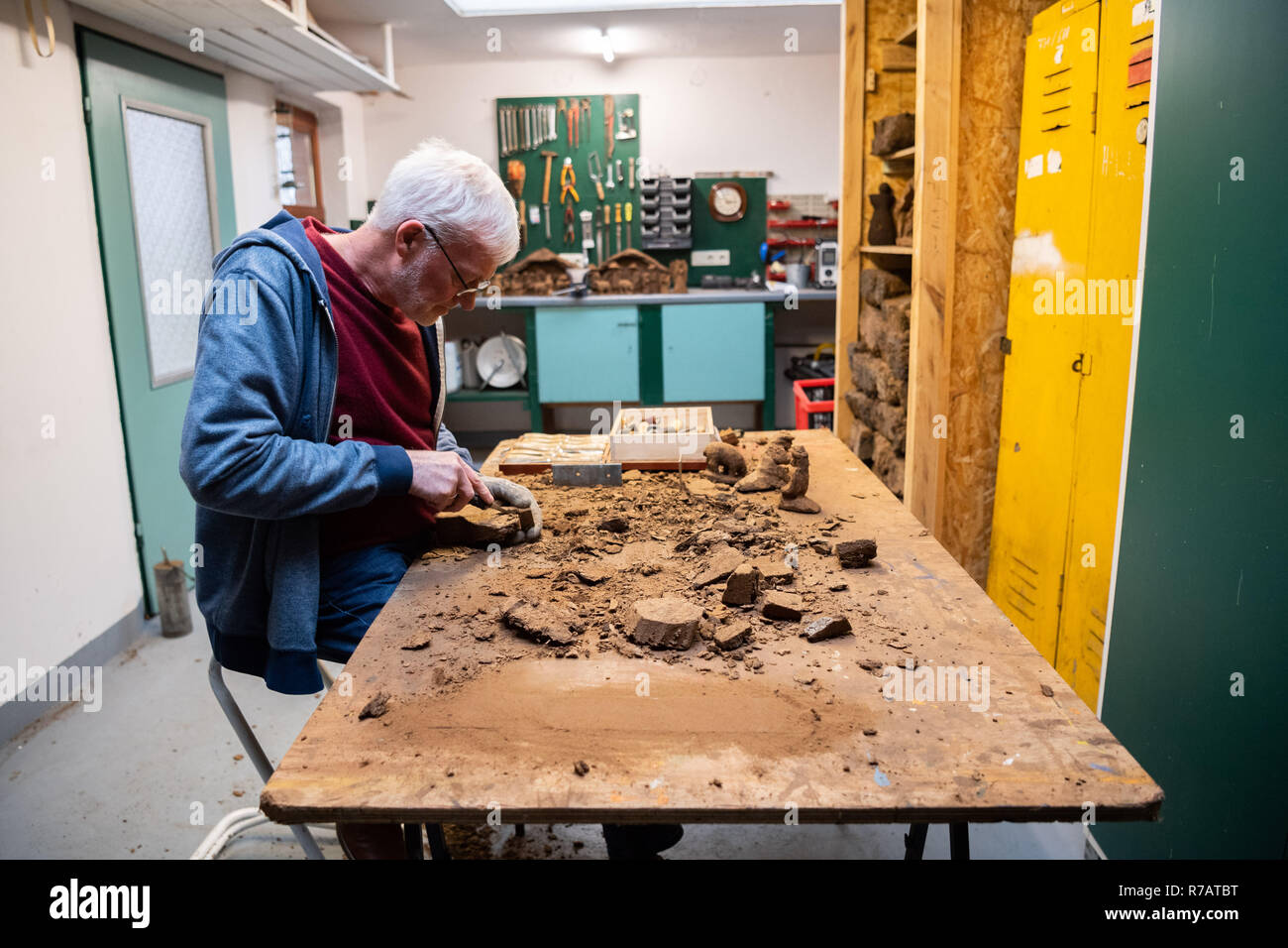 "Saterland, Germany. 22nd Nov, 2018. Karl-Heinz Brinkmann carves a Christmas figure from peat in his home workshop. The 64 year old Saterland artist works with many materials. But the dried white peat is special: it is 2000 years old. (to dpa ""2000 years old: Christmas cribs from peat"" from 09.12.2018) Credit: Mohssen Assanimoghaddam/dpa/Alamy Live News Stock Photo"