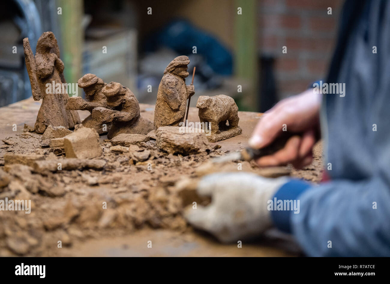Saterland, Germany. 22nd Nov, 2018. Christmas figures made of peat stand on a table in the workshop of Karl-Heinz Brinkmann, while Brinkmann carves a piece of peat. The 64 year old Saterland artist works with many materials. But the dried white peat is special: it is 2000 years old. (to dpa '2000 years old: Christmas cribs from peat' from 09.12.2018) Credit: Mohssen Assanimoghaddam/dpa/Alamy Live News - Stock Image