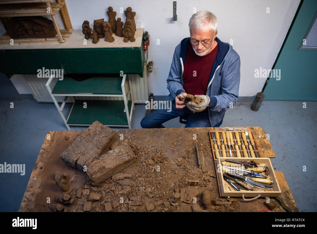 Saterland, Germany. 22nd Nov, 2018. Karl-Heinz Brinkmann carves a Christmas figure from peat in his home workshop. The 64 year old Saterland artist works with many materials. But the dried white peat is special: it is 2000 years old. (to dpa '2000 years old: Christmas cribs from peat' from 09.12.2018) Credit: Mohssen Assanimoghaddam/dpa/Alamy Live News - Stock Image