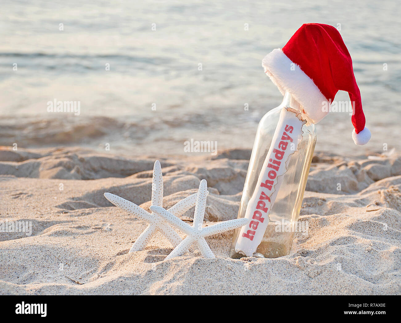 e5c3e378 Santa hat on message in a bottle with pair of white starfish in beach sand  and