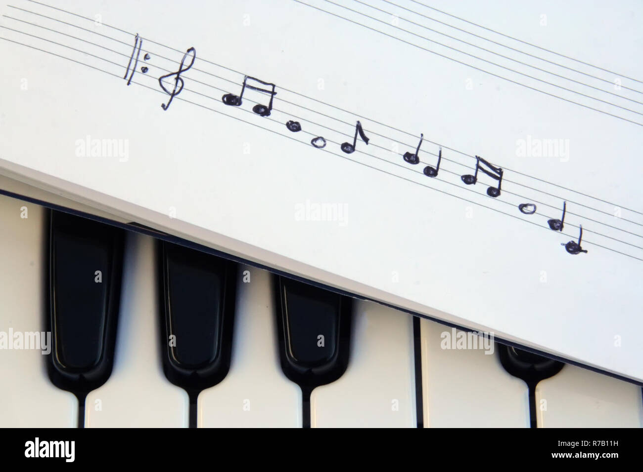 Piano keyboard and musical notes. Musical notes on a piano keyboard. - Stock Image