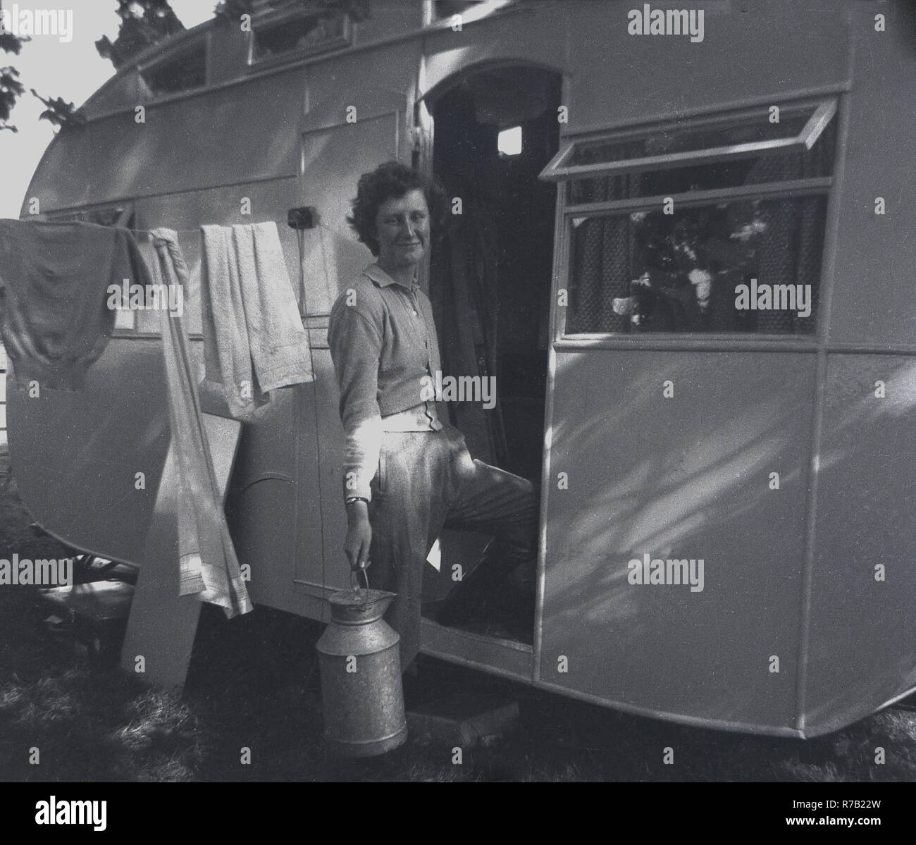 1940s, lady holding a metal milk churn at the door to her caravan with clothes hanging on a washing line, England, UK. Stock Photo