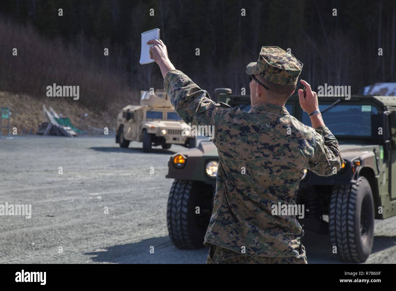 U.S. Marine Corps Cpl. Buck Ems, a Landing Support Specialist with 2nd Transportation Support Battalion, guides Humvees to park in the assembly area following a convoy at Strategic Mobility Exercise 17 (STRATMOBEX) near Stjørdal, Norway, May 3, 2017. During this exercise Marines pulled vehicles from caves of the Marine Corps Prepositioning Program in Norway (MCPP-N). MCPP-N provides an alternative to shipping equipment from the United States in order to decrease operation response times. Stock Photo