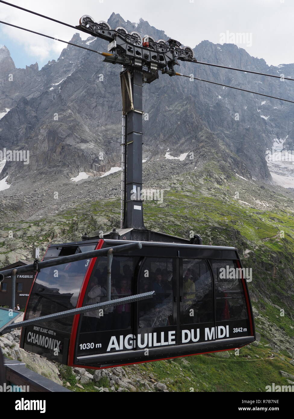 Cable car cabin with tourists on AIGUILLE DU MIDI at high french mountain range landscape at european ALPS - vertical - Stock Image