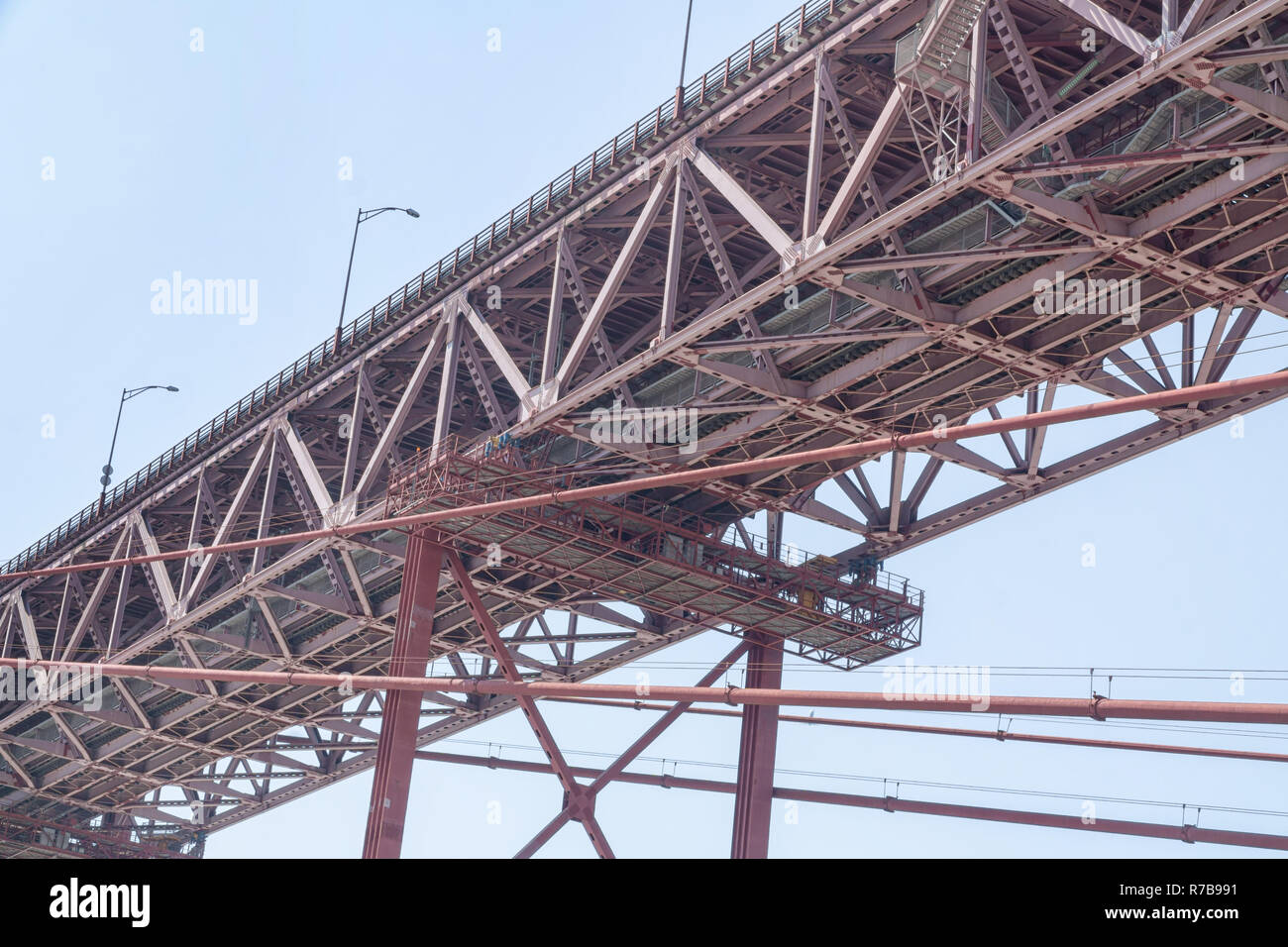 Bottom view of the structure of suspension bridge. Famous 25th of April Bridge over Tagus River in Lisbon, Portugal. - Stock Image