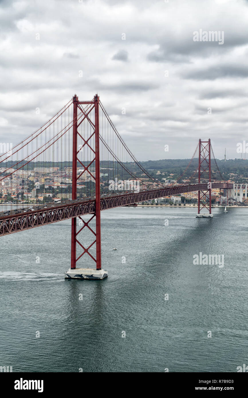 Famous 25th of April Bridge over Tagus River in Lisbon, Portugal on a cloudy day. View from the left (south) bank of the Tagus river. - Stock Image