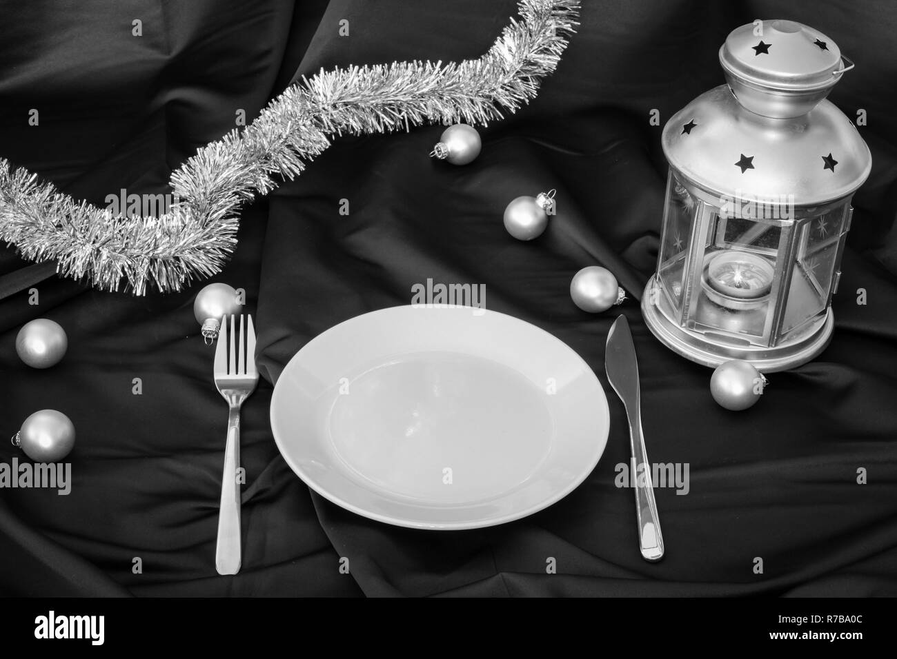 empty plate on dark linen with christmas balls and lantern Stock Photo
