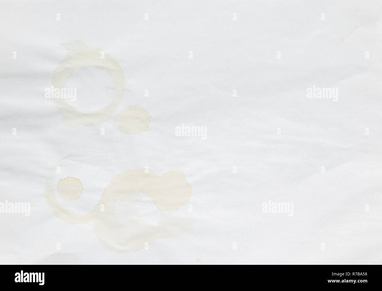 Full frame background of faded coffee cup stains on an old and uneven white paper sheet. - Stock Image