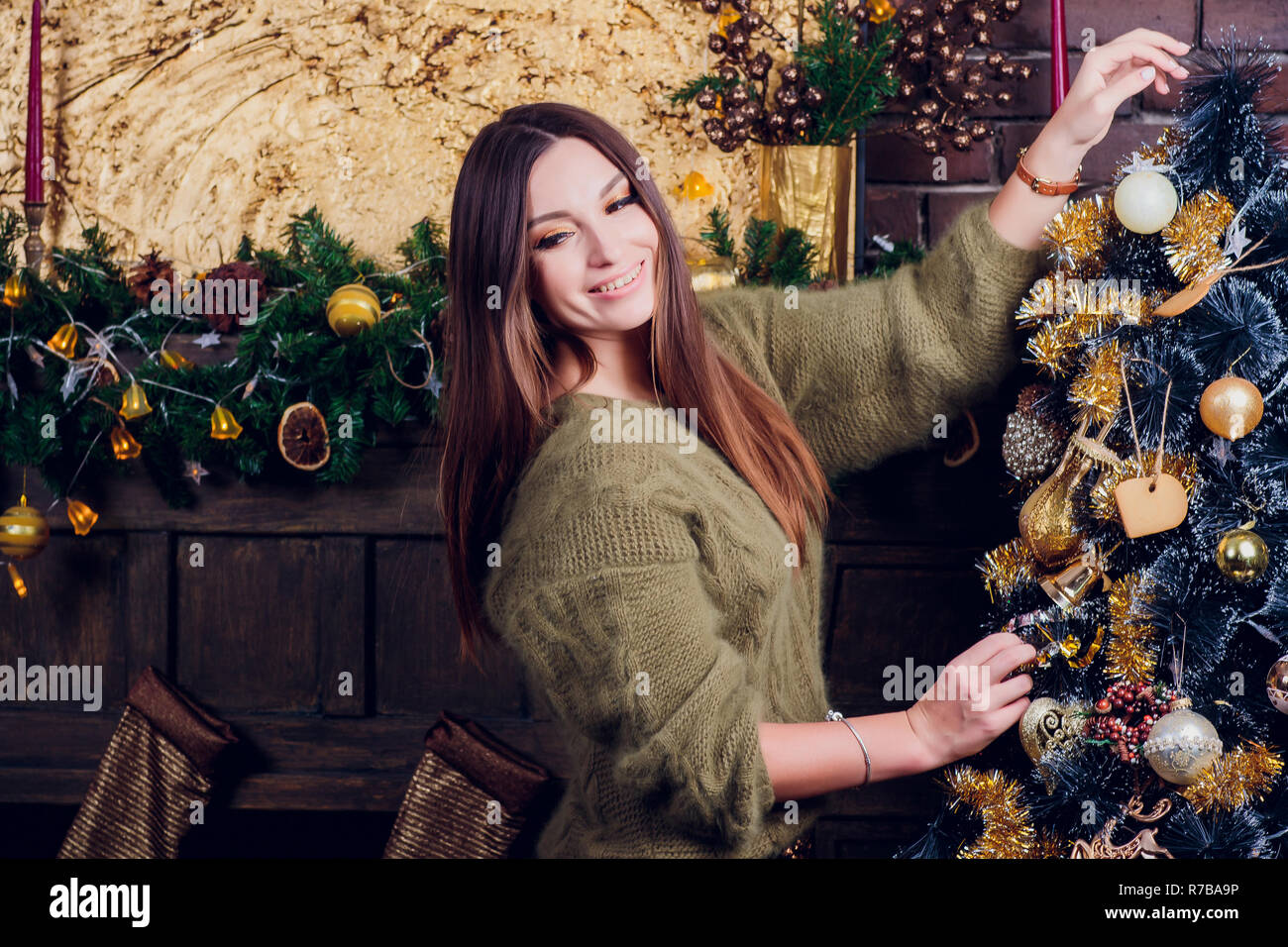 A teenage girl with long brown hair and green comfy sweater sitting and looking sideways. - Stock Image
