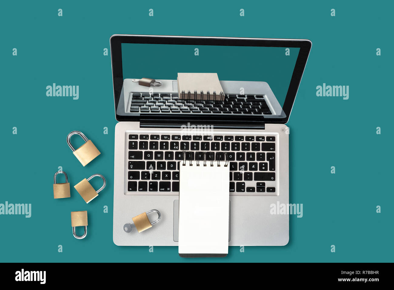 Top view of a laptop, padlocks and a notepad with copyspace, a security concept Stock Photo