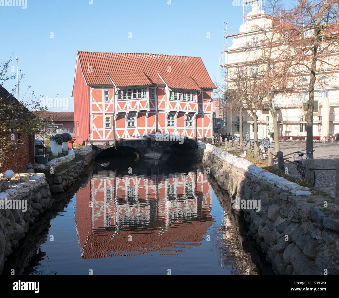 Historical half-timbered house, called Brueckenhaus (bridge house), spans the canal to the harbor of Wismar in Mecklenburg-Vorpommern, Northern German - Stock Image