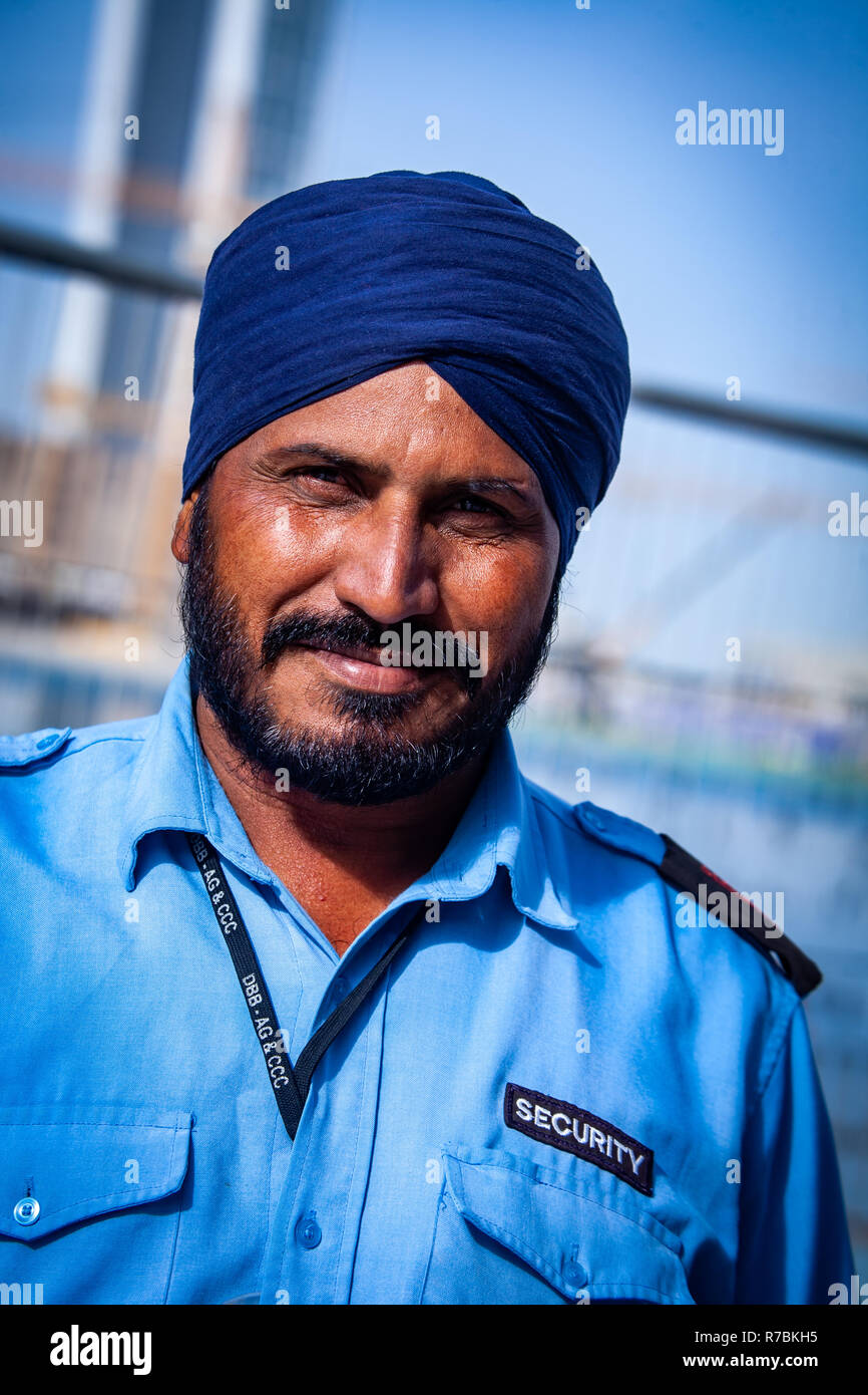 Security man wearing a turban headdress working on a construction site in Dubai, UAE - Stock Image